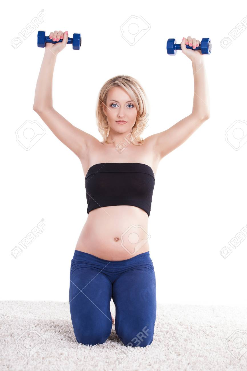 4a8145c9d79 A pregnant woman exercising with a light weights - isolated. Workout  indoors