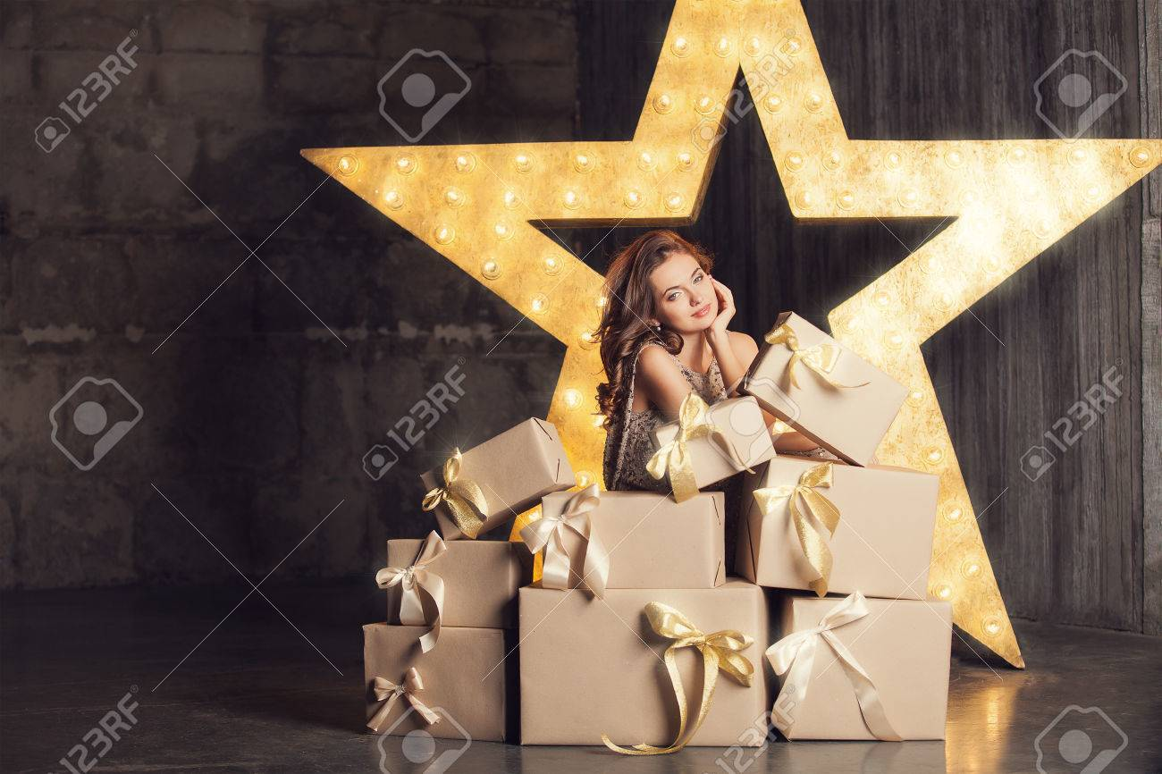 Fashion woman with lots of gifts. Brodway star on background - 32261901