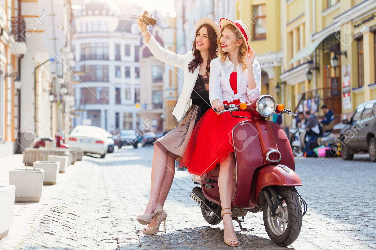 Two beautiful girls in urban background smiling with old scooter - 58119282