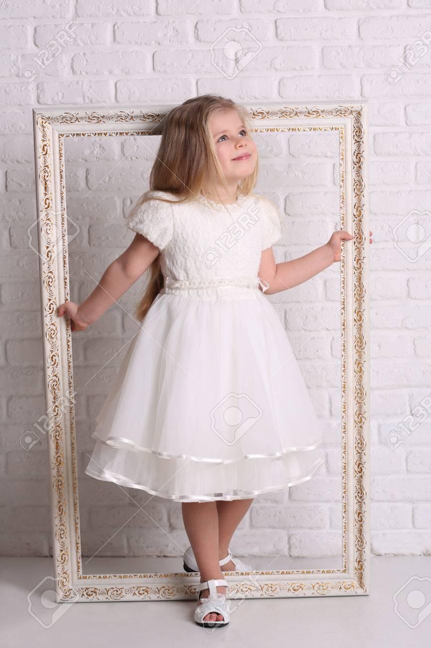 Kleines Mädchen Hält Rahmen, Textur Hintergrund, Weiße Mauer, Kleid ...