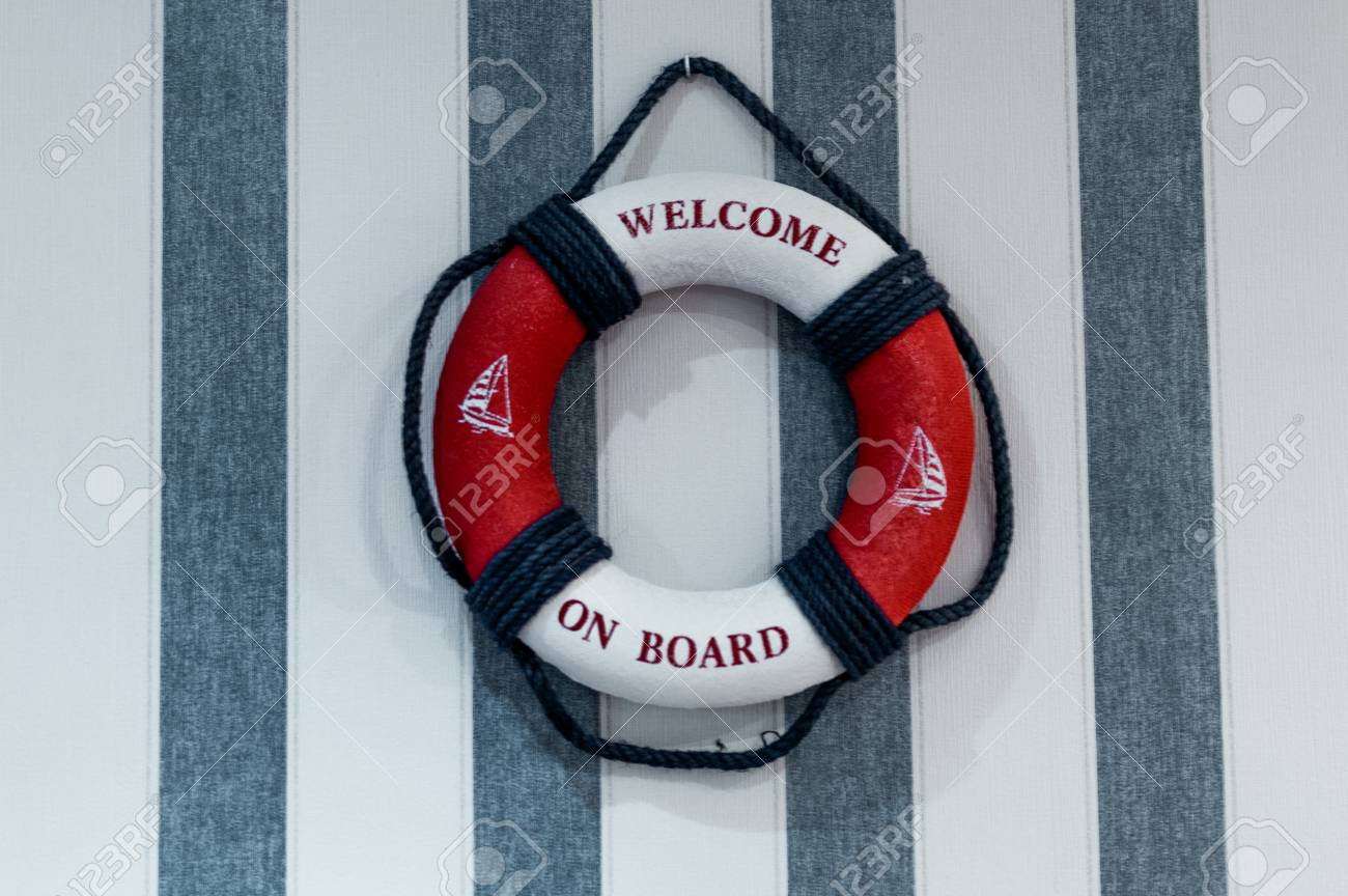 c0d74d581850 Red lifebuoy with welcome aboard hanging on wall with blue white stripes  Stock