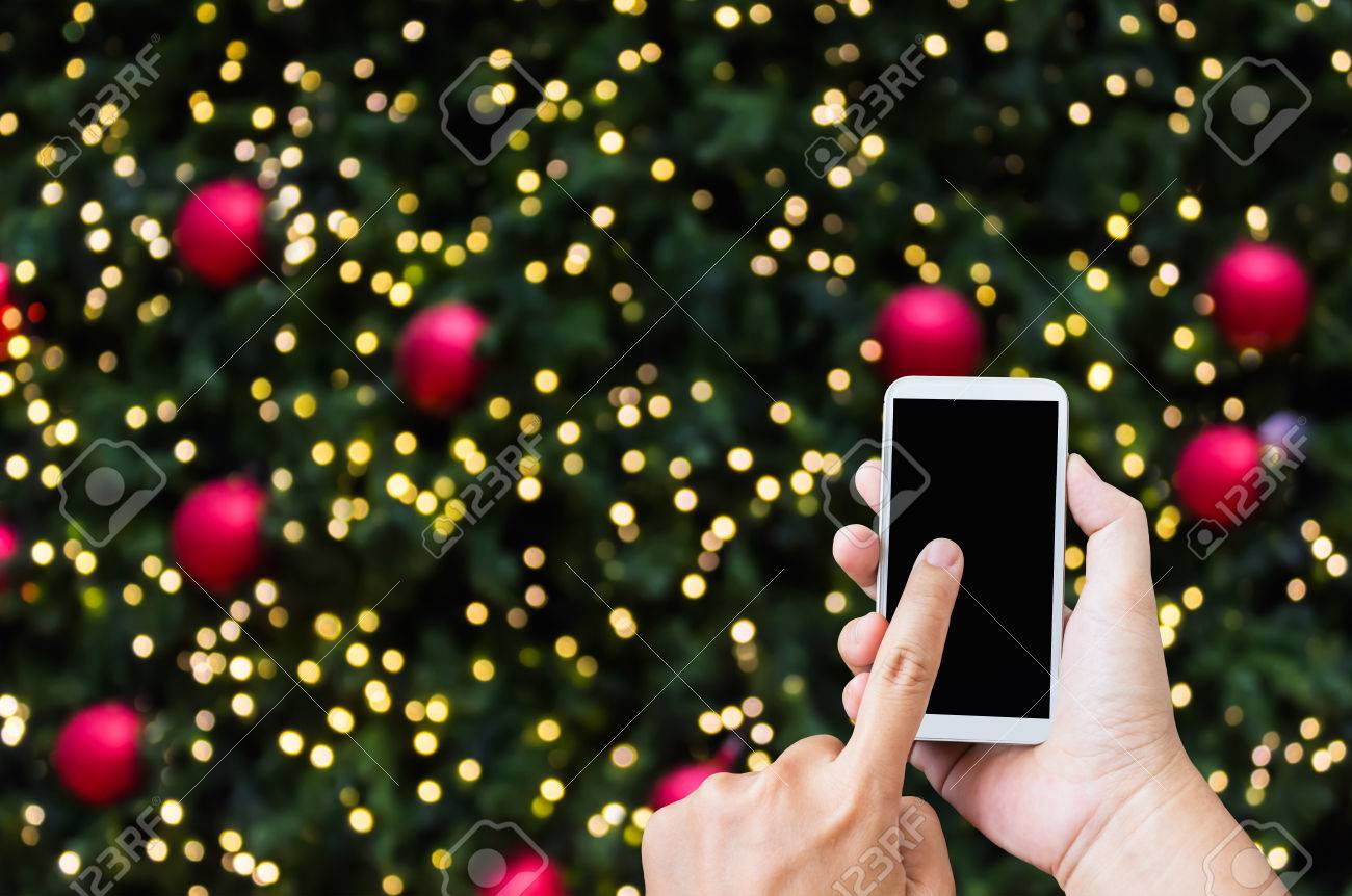 hand press on big blank smartphone screen or mobile phone on xmas new year theme golden