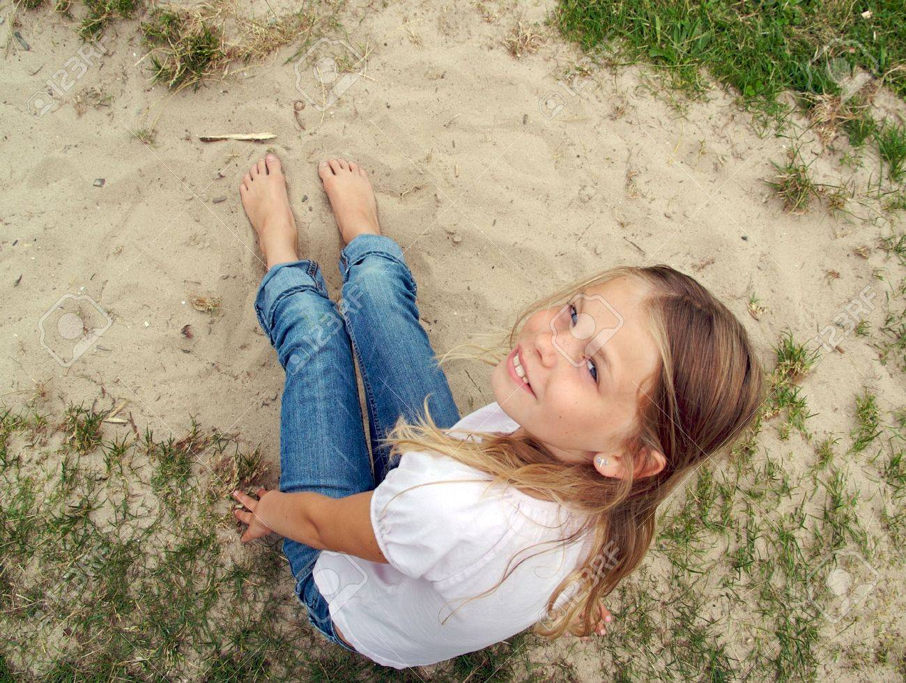 a young girl with bare feet in the sand stock photo picture and