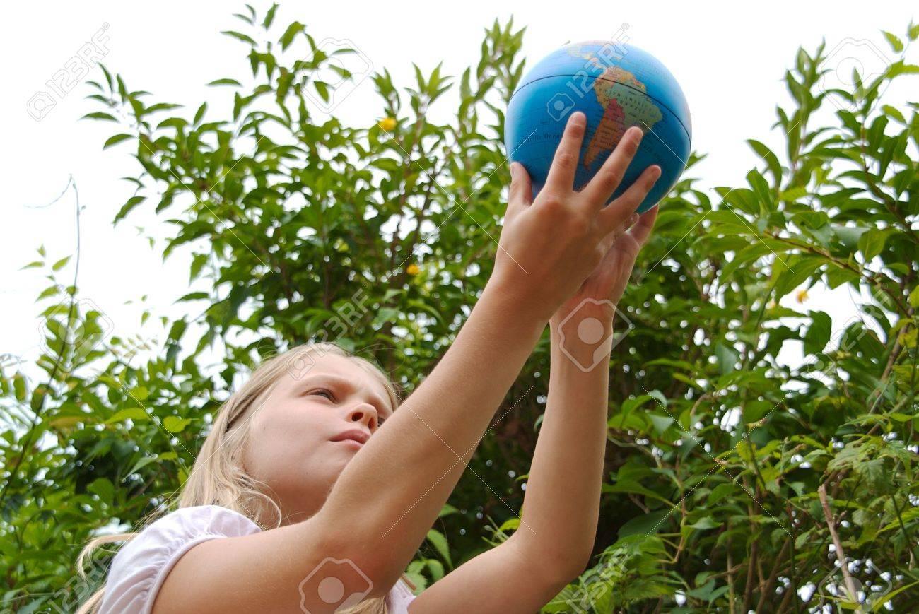 Una joven está sosteniendo el mundo en sus manos Foto de archivo - 5400369