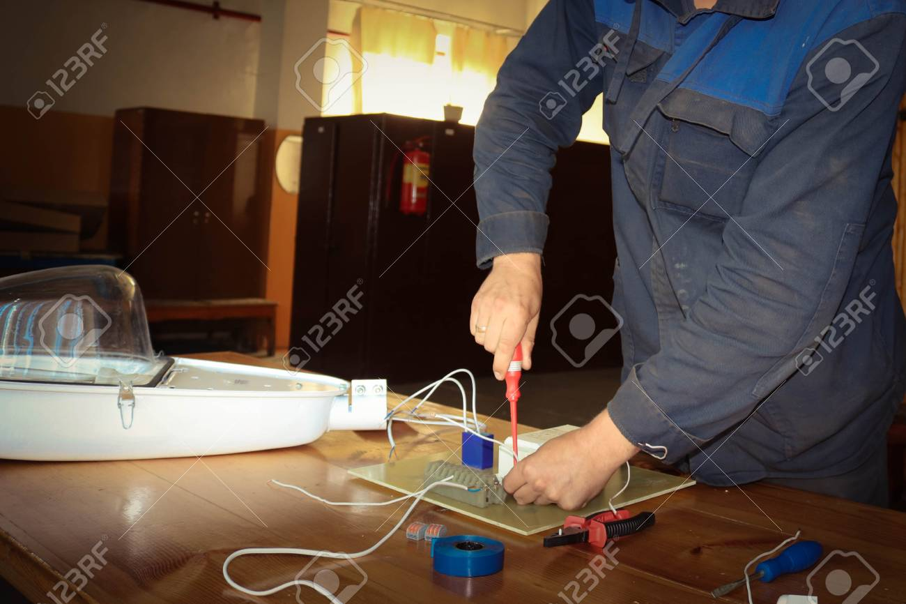 A Man Working Electrician Works Collects The Electric Circuit Of How Does Work Large White Street Lamp