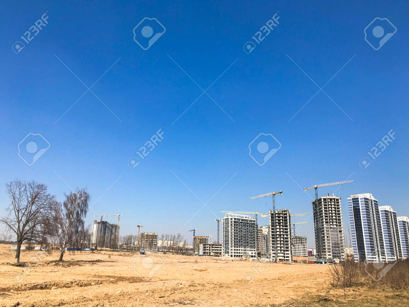Building with the help of construction cranes of high reinforced concrete, panel, cast-frame, frame-block houses, buildings, skyscrapers, new buildings on the background of sandy land. - 120667640