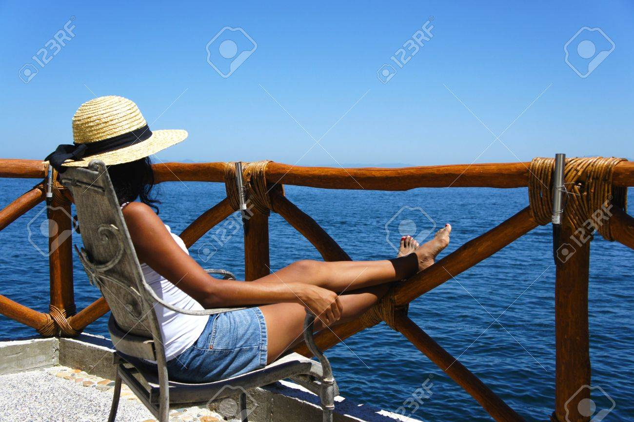 Young woman sitting on a balcony looking over the ocean enjoying the view Stock Photo - 13142697