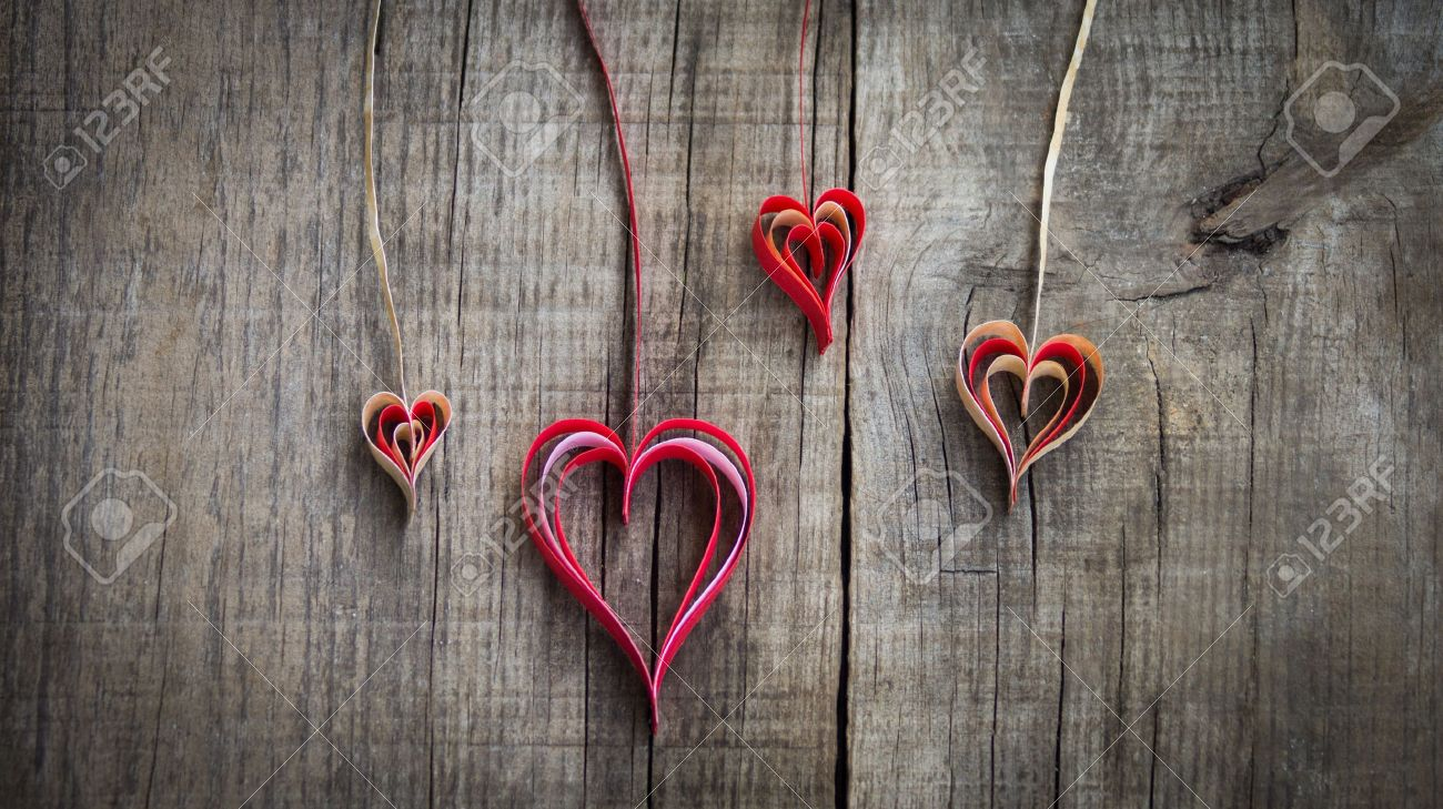 Hanging paper heart decoration on wood background. - 22025608