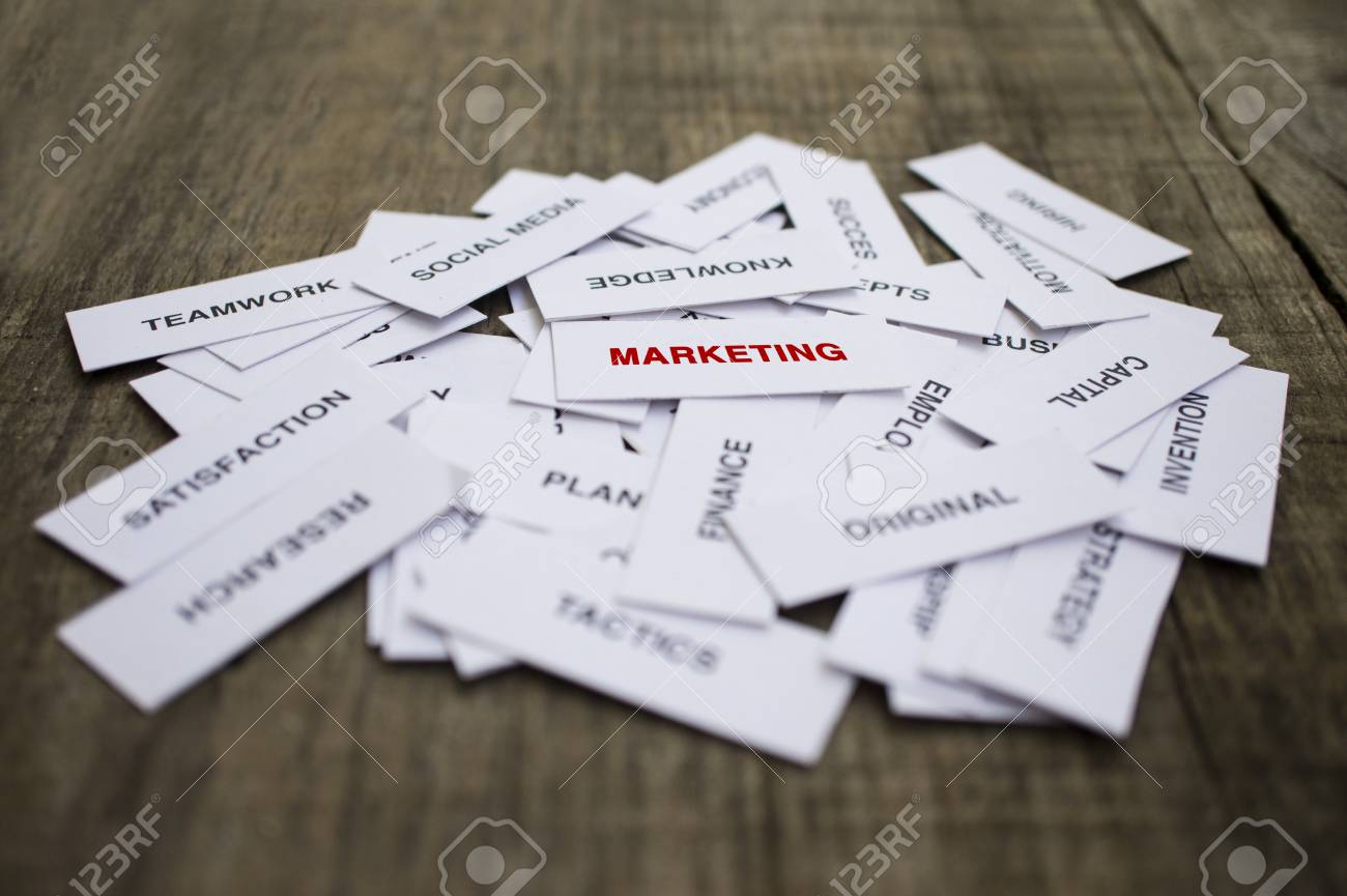 Paper strips with Marketing related words on wooden background Stock Photo - 23330204