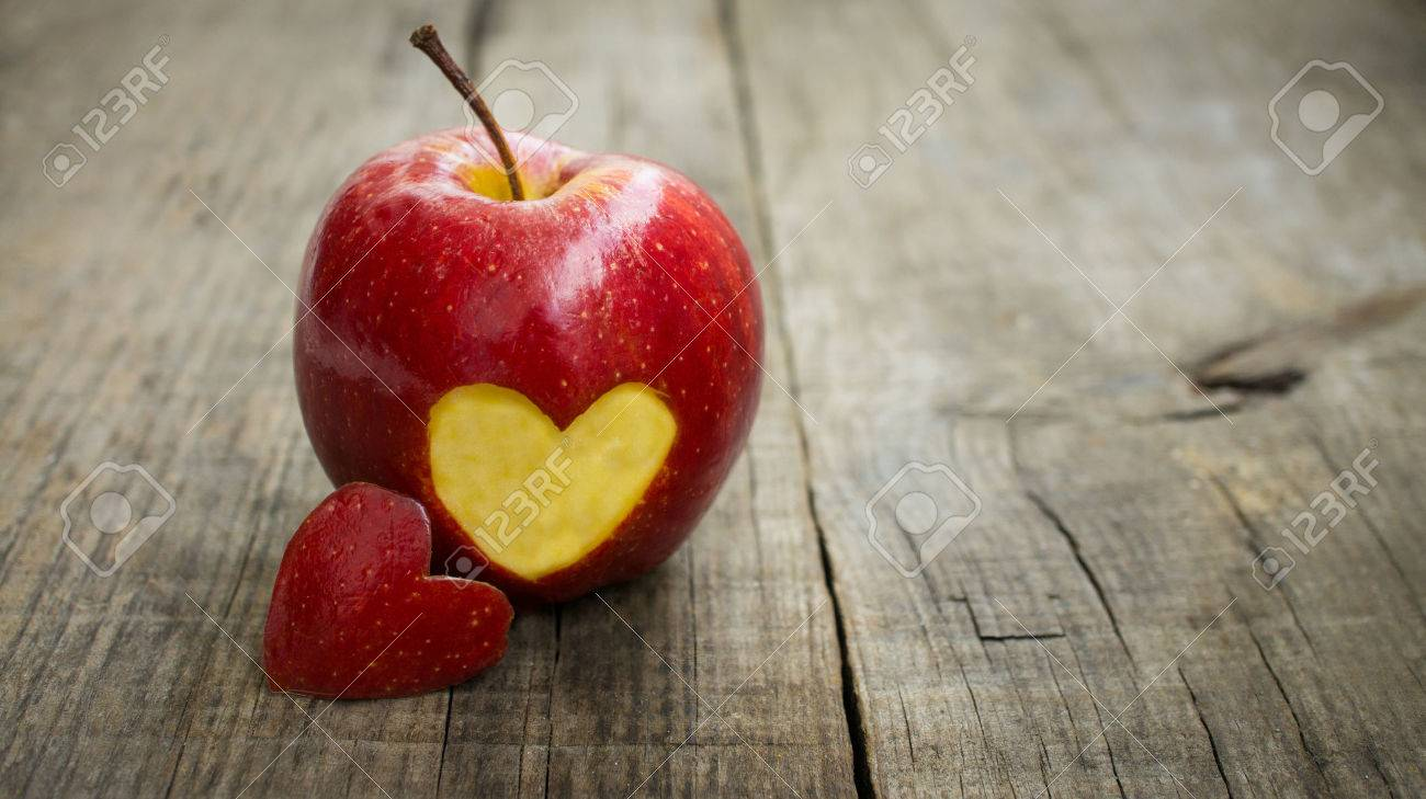 A red apple with engraved heart on wood background Stock Photo - 23479026
