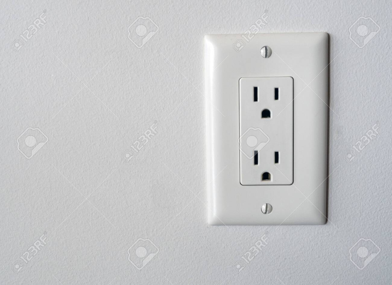 Isolated North American power outlet plug in socket on a white wall background Type B style - 129074139