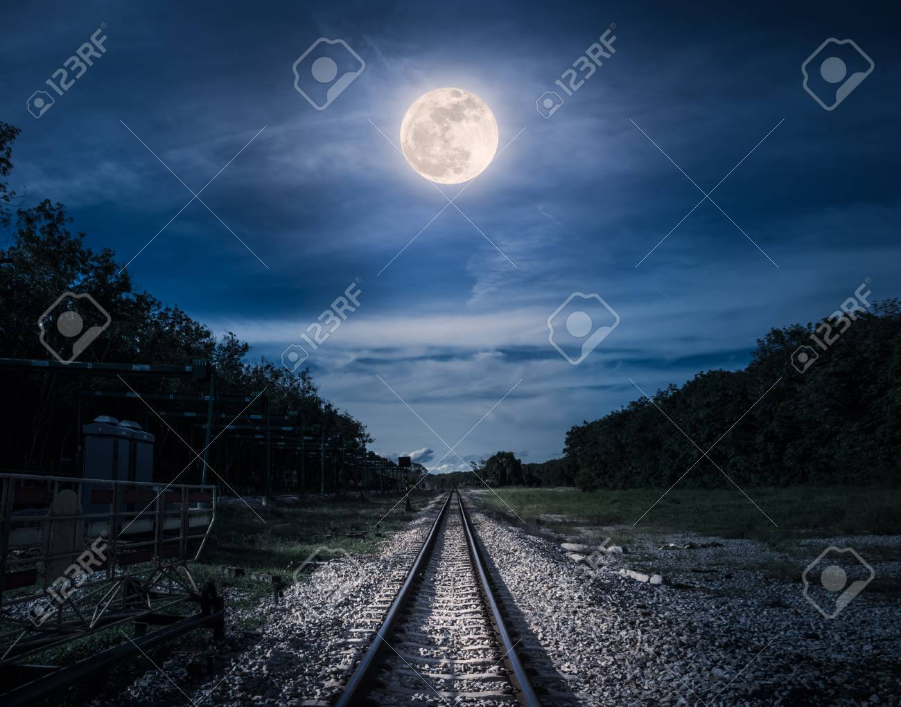 Railroad tracks through the woods at night. Beautiful blue sky and full moon above silhouettes of trees and railway. Serenity nature background. Outdoor at nighttime. The moon taken with my own camera - 89557452