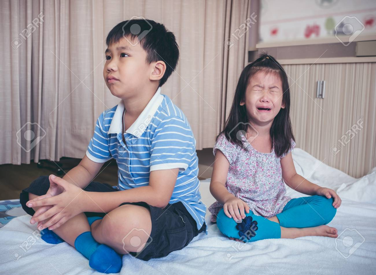 Quarreling conflict of children. Asian girl has problem between brother and scream crying with tears, sadden boy sitting near by. Relationship difficulties in family concept. - 92492628