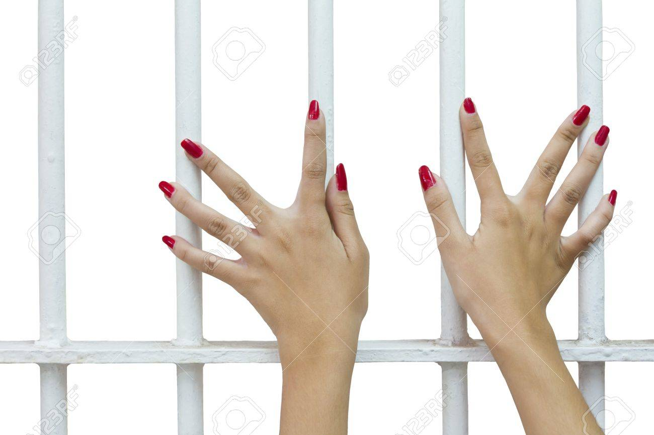 Isolates of woman fingers with red nails holding grip on the bars of the cage Stock Photo - 17821029