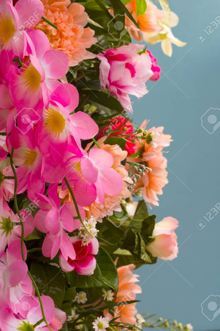 Pink bouquet of fake flowers which bloom beautiful wall hanging pink bouquet of fake flowers which bloom beautiful wall hanging blue background stock photo izmirmasajfo