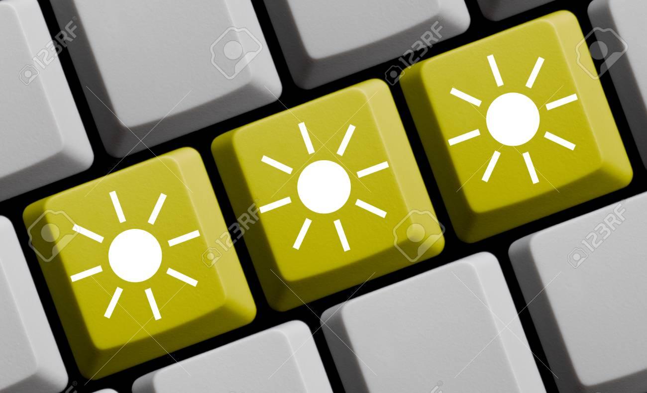 Three White Sun Symbols On Yellow Computer Keyboard Stock Photo
