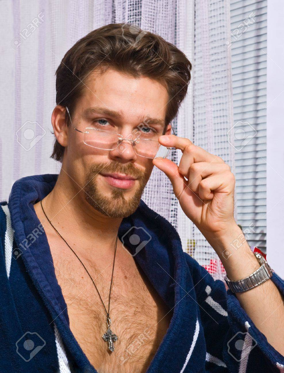 Young man wearing blue striped bathrobe puts on his glasses Stock Photo - 4072635