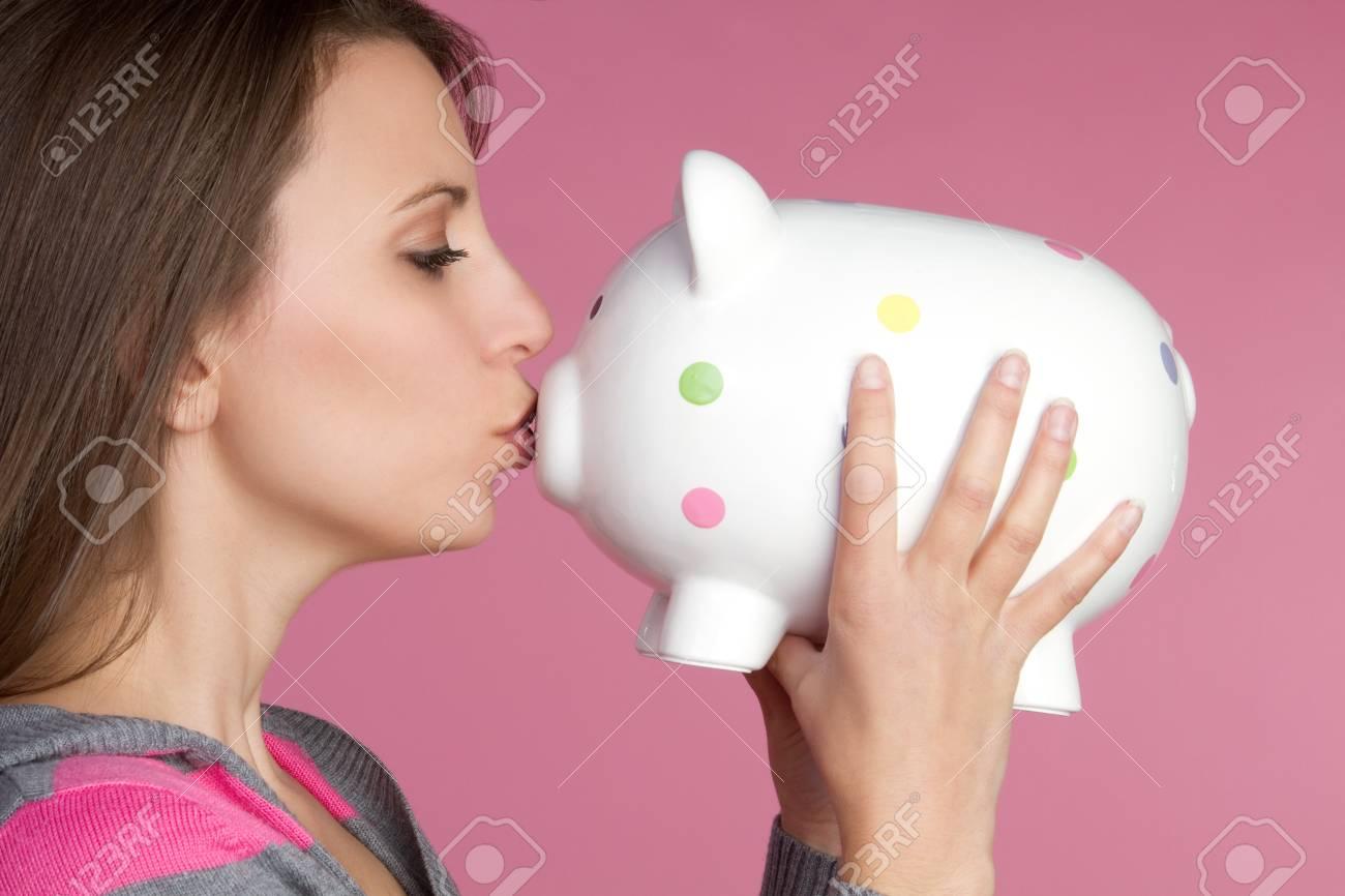 Pretty girl kissing piggy bank Stock Photo - 9397193