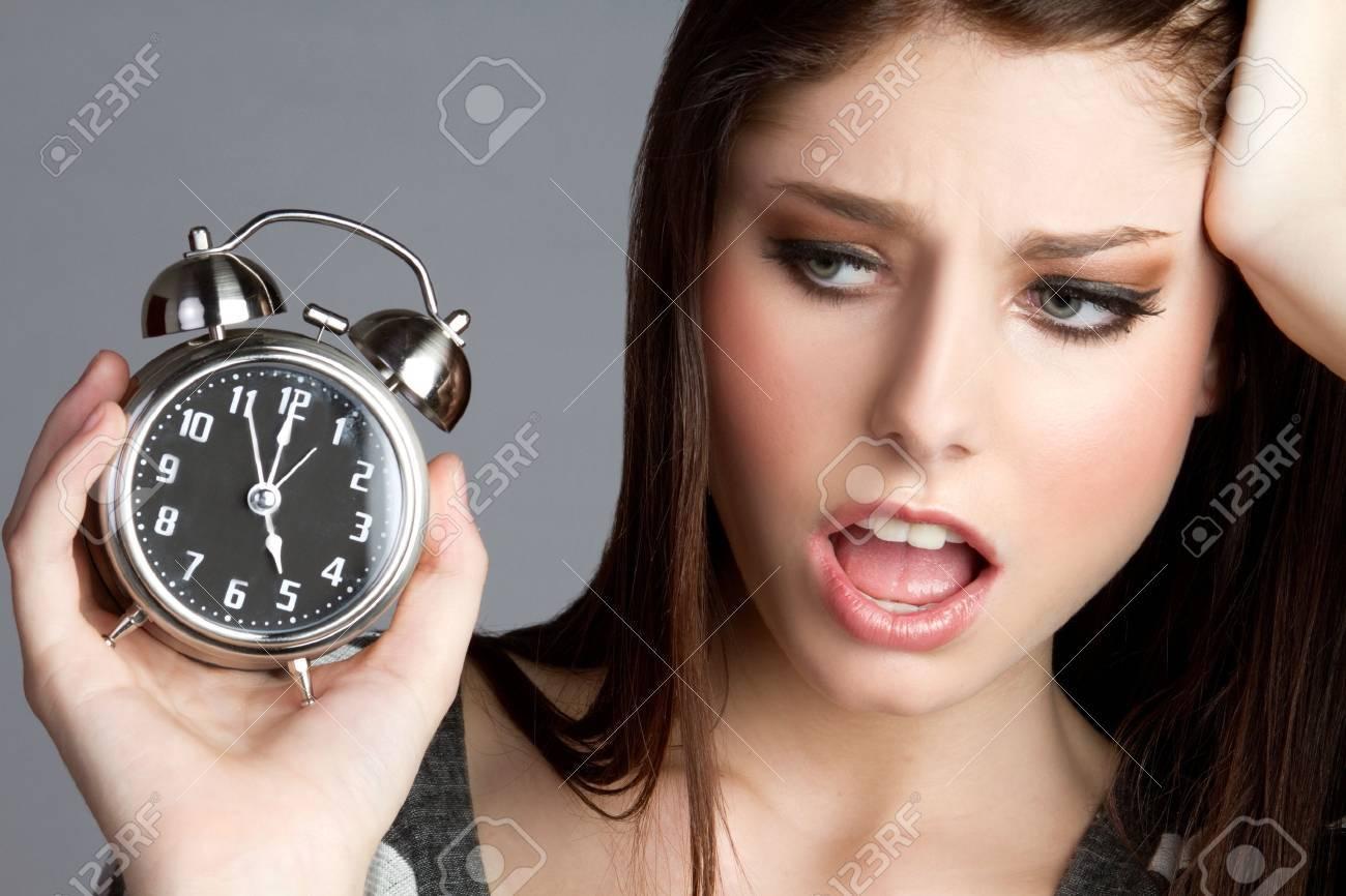 Annoyed woman holding alram clock - 9466097