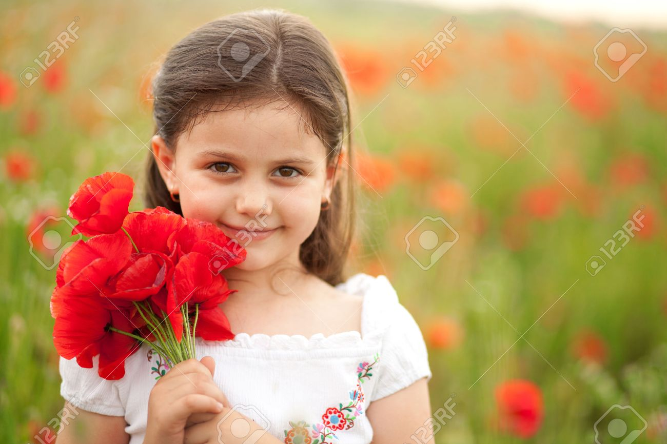 close up of cute girl in poppy field holding flowers bouquet