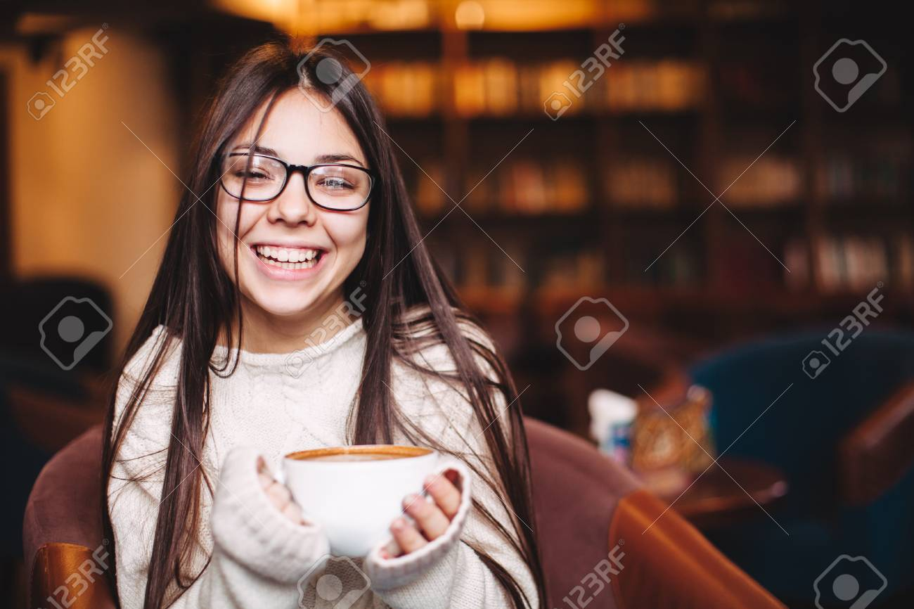 6fc904edb0e5 Pretty smiling girl wearing eyeglasses sitting and holding a cup of coffee  with copyspace. Happy