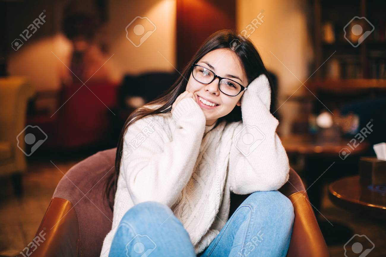 85f72299fda7 Cute teenage girl wearing glasses sitting in cafe,smiling, relaxing. Stock  Photo -