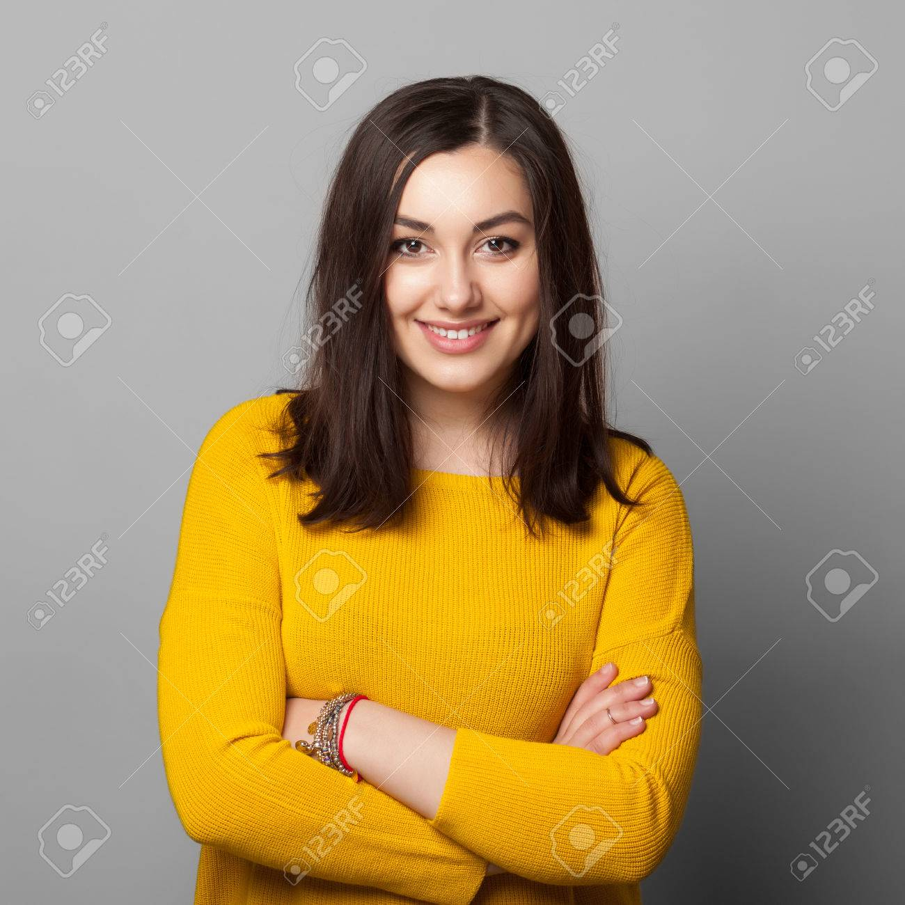 Smiling business woman with folded hands against grey background. Toothy smile, crossed arms. - 51671081