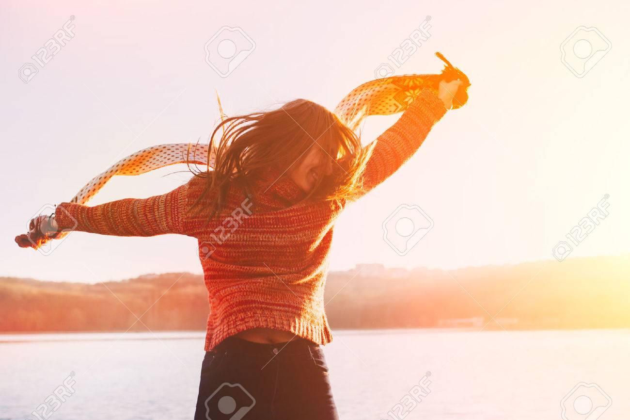 Positive young girl wearing warm winter clothes having fun at lake. - 52084951
