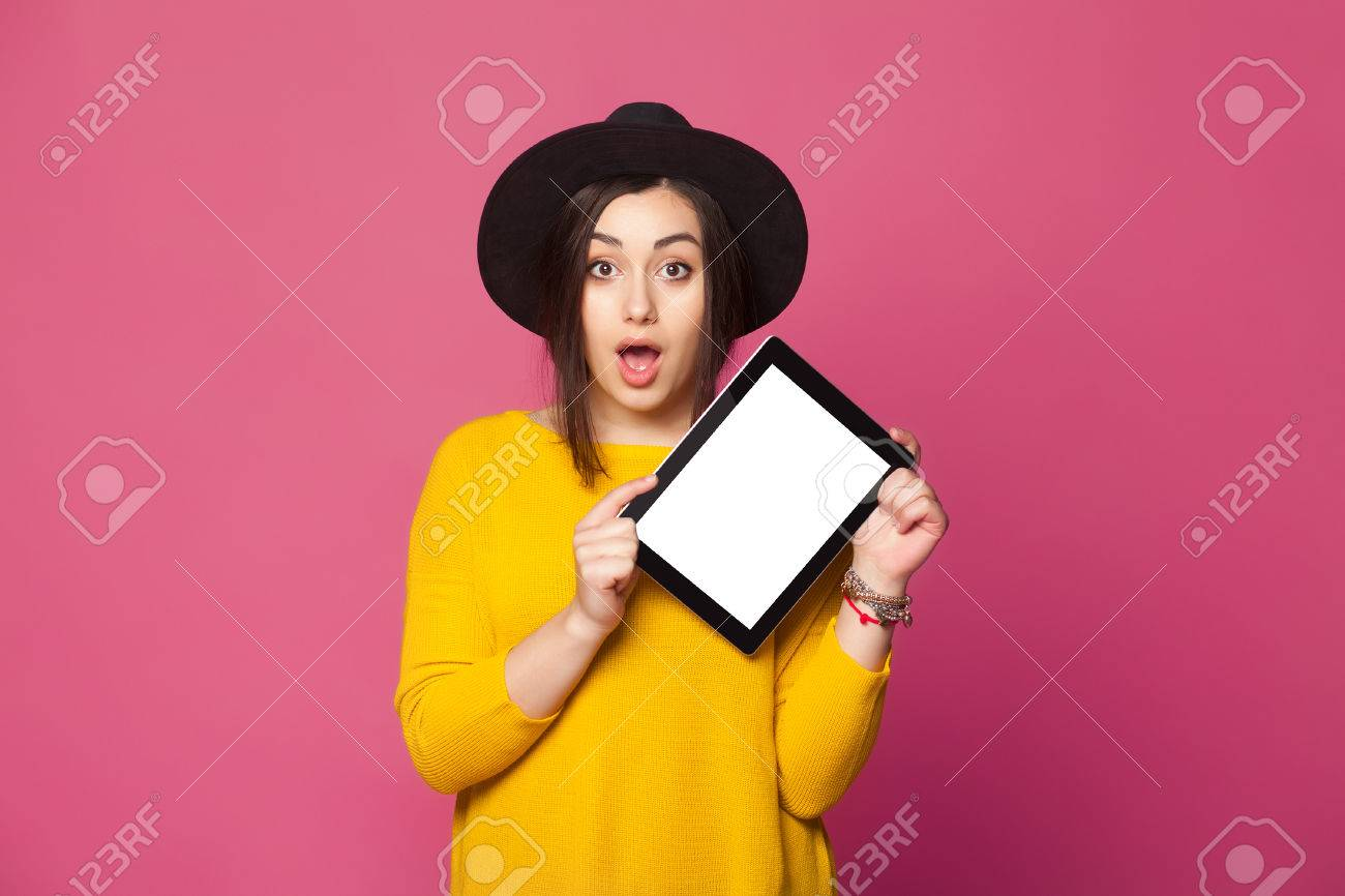 Portrait of amazed young woman showing tablet computer screen isolated on a pink background - 53648944