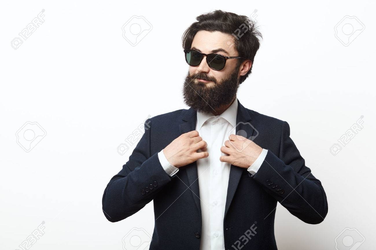 Portrait of happy hipster guy wearing a business black suit. fashion bearded male model posing isolated over white background. - 56241152