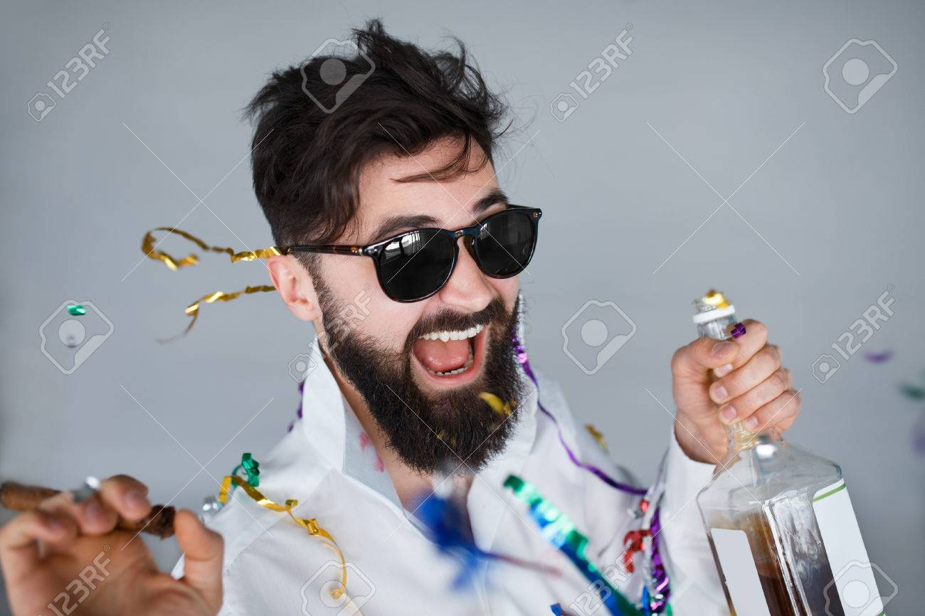 Bearded man with sunglasses holding a bottle of alcohol and cigar at celebration. Ecstatic portrait of drunk man having fun at wild party - 57074559