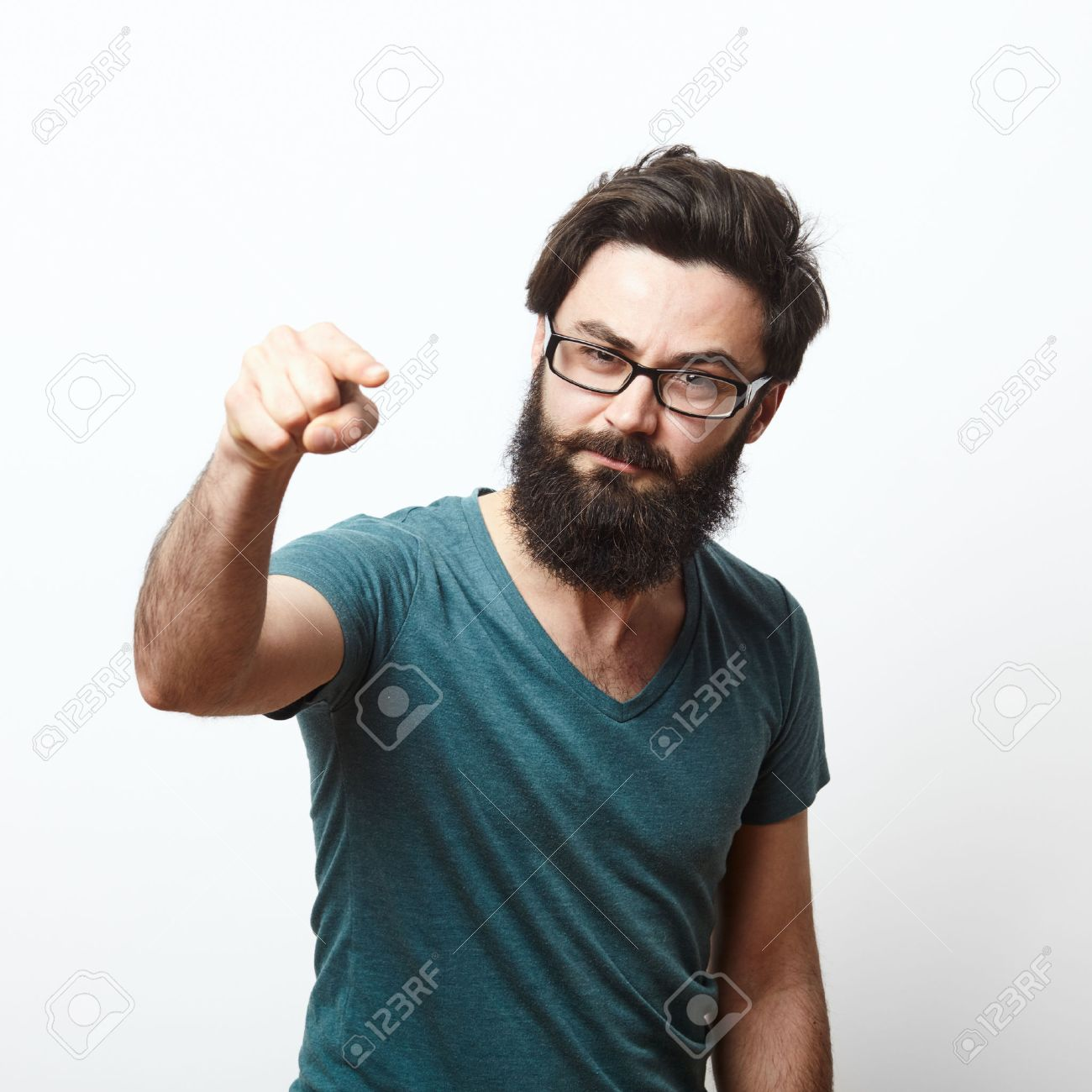 portrait of a angry young man with beard and glasses wearing t-shirt pointing to camera. We need you concept - 57775863