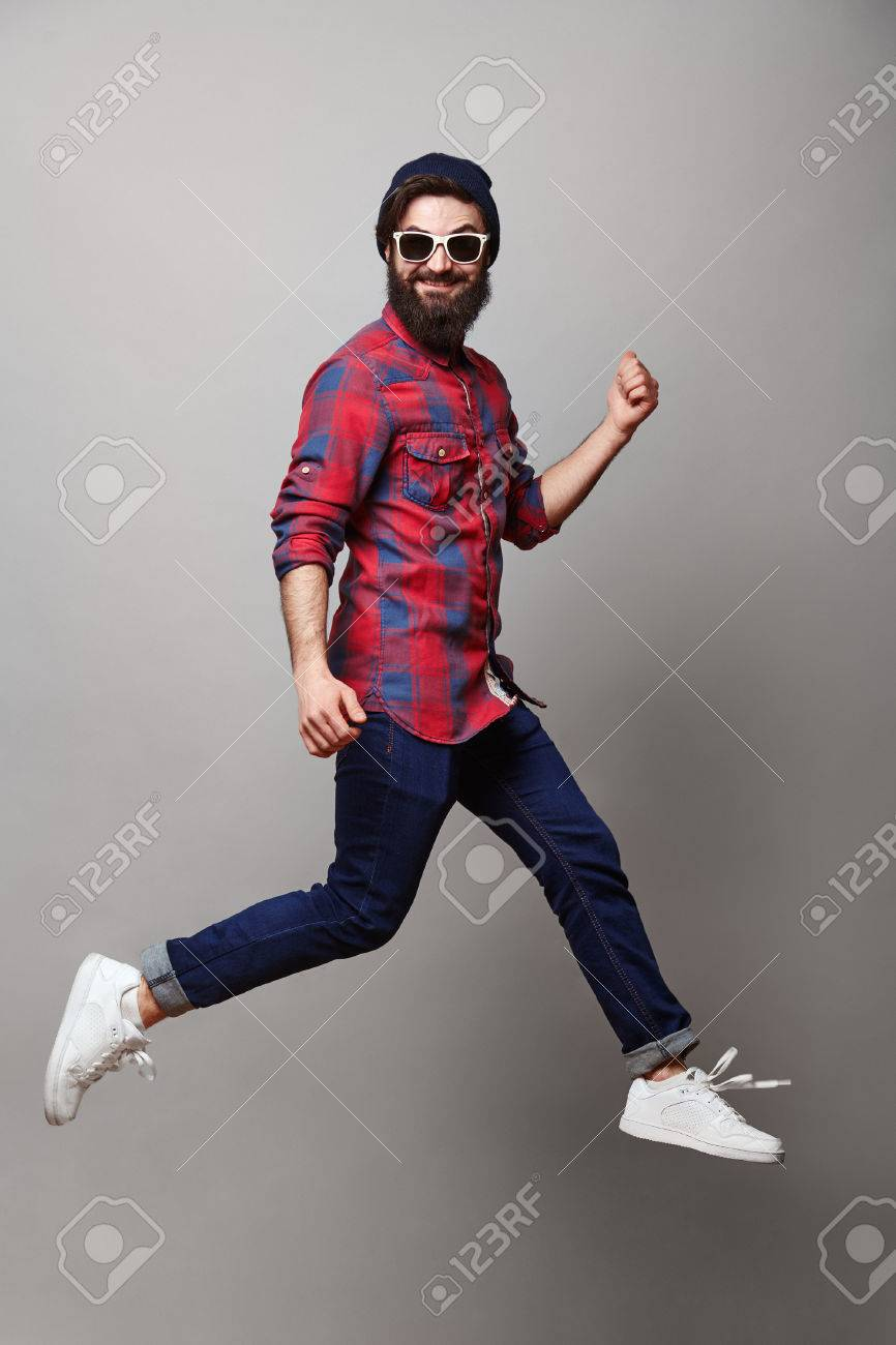 happy excited jmping young bearded man. Funny portrait on young casual male model in humorous jump on grey background. - 57775868