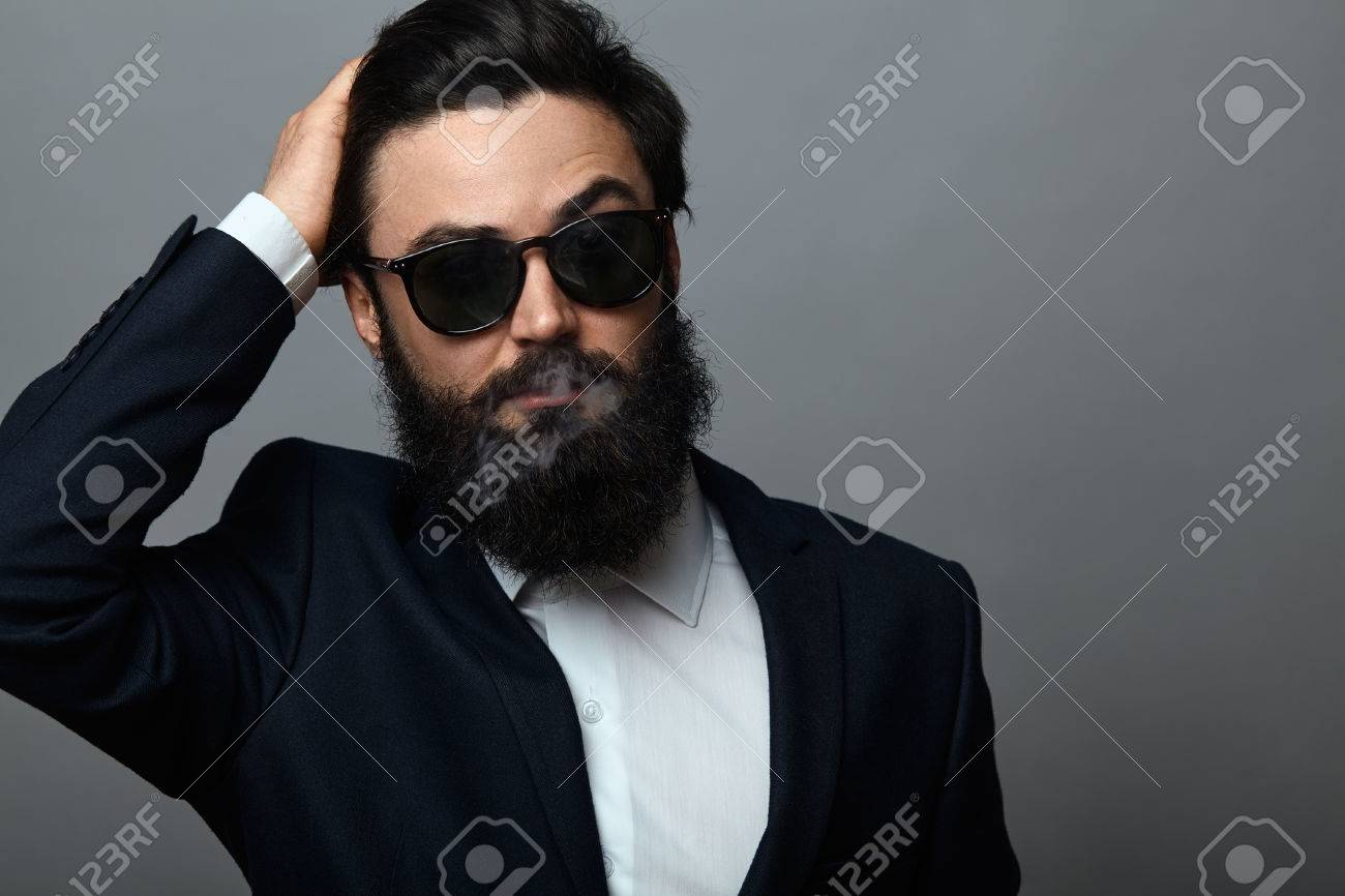 eb038d1922ae handsome bearded man in black suit and sunglasses posing against grey  background. Confident serious business