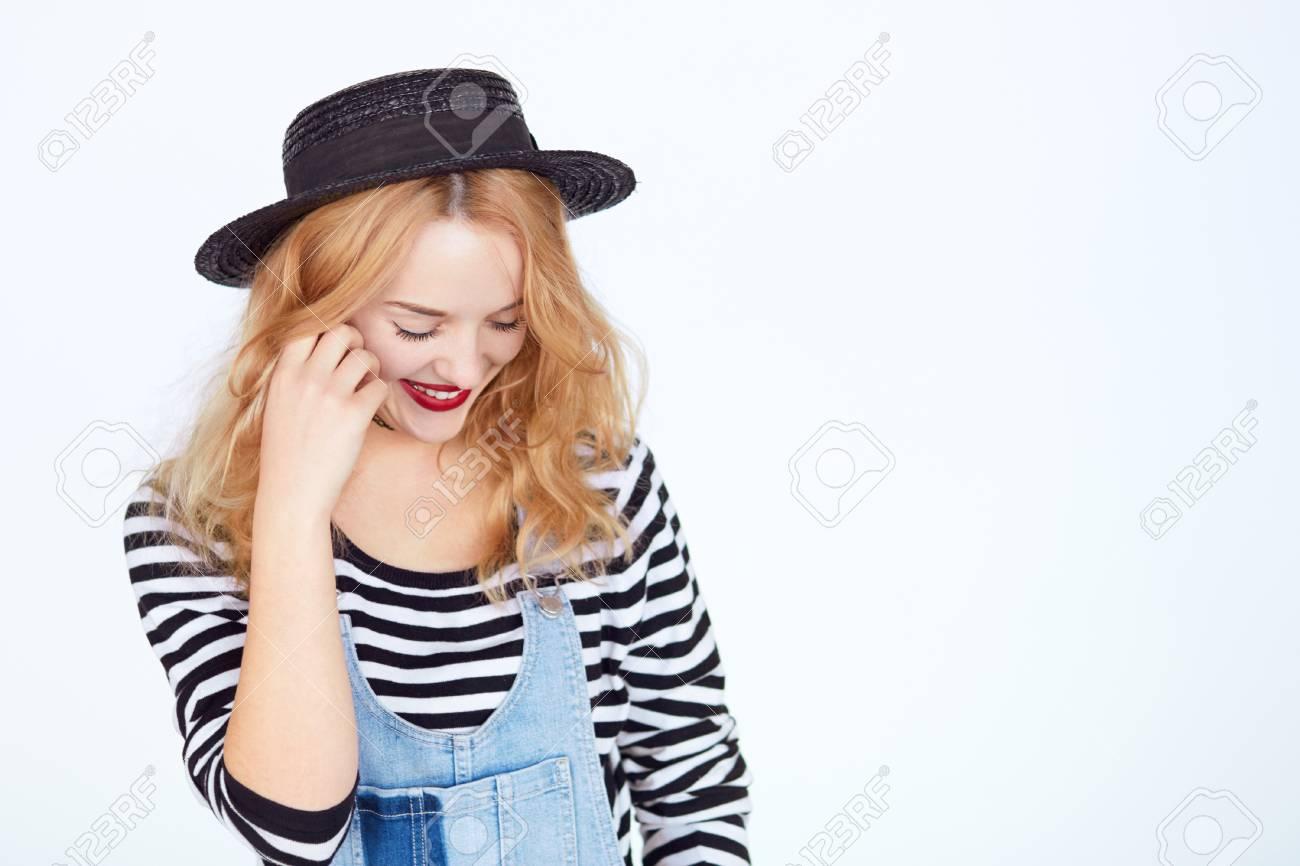 Archivio Fotografico - Ritratto di una bella ragazza timida giovane bruna isolato  su sfondo bianco con copyspace Giovane donna in cappello alla moda e jeans  ... 4f615d643c0b