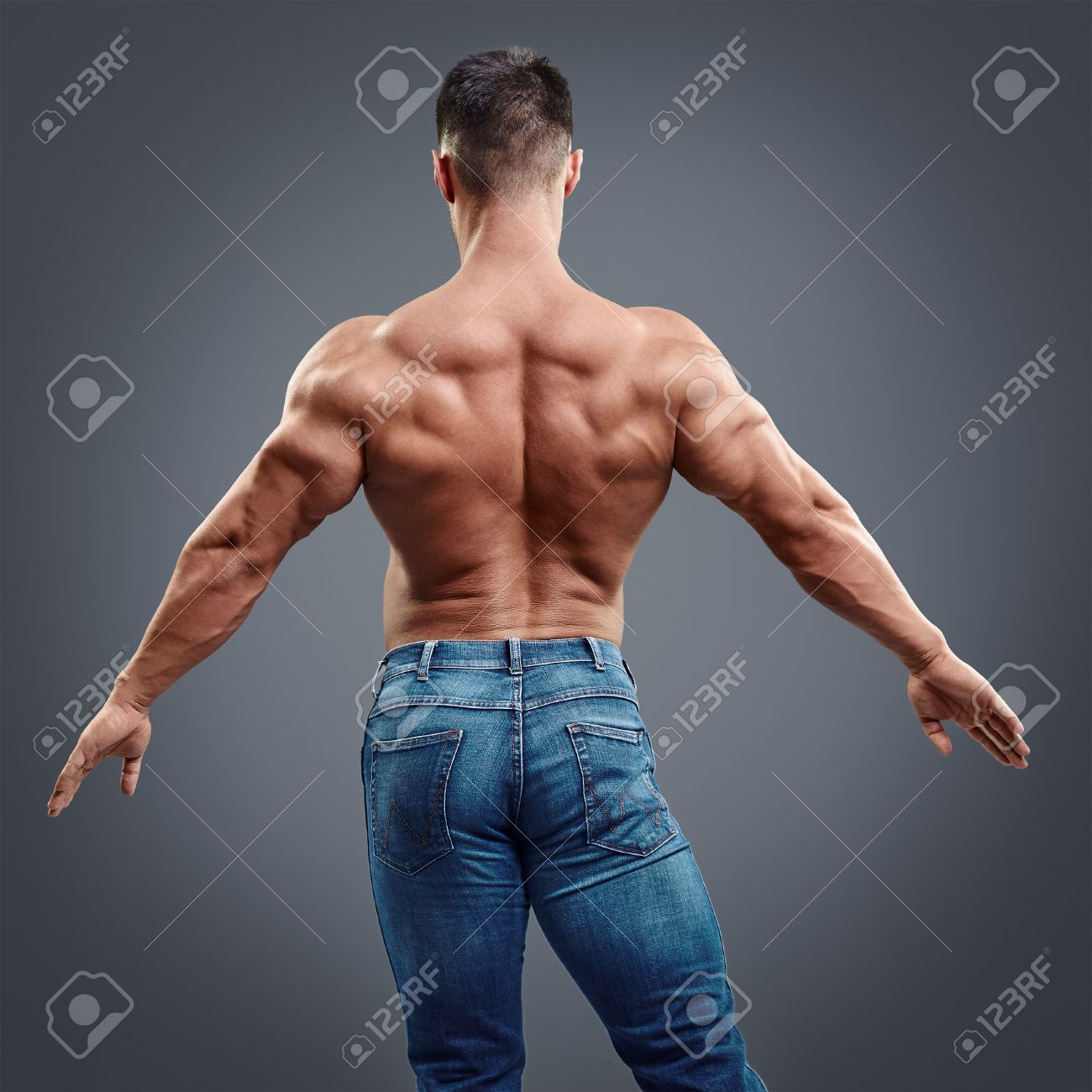 Male Bodybuilder Flexing His Back Muscles On Grey Background ...