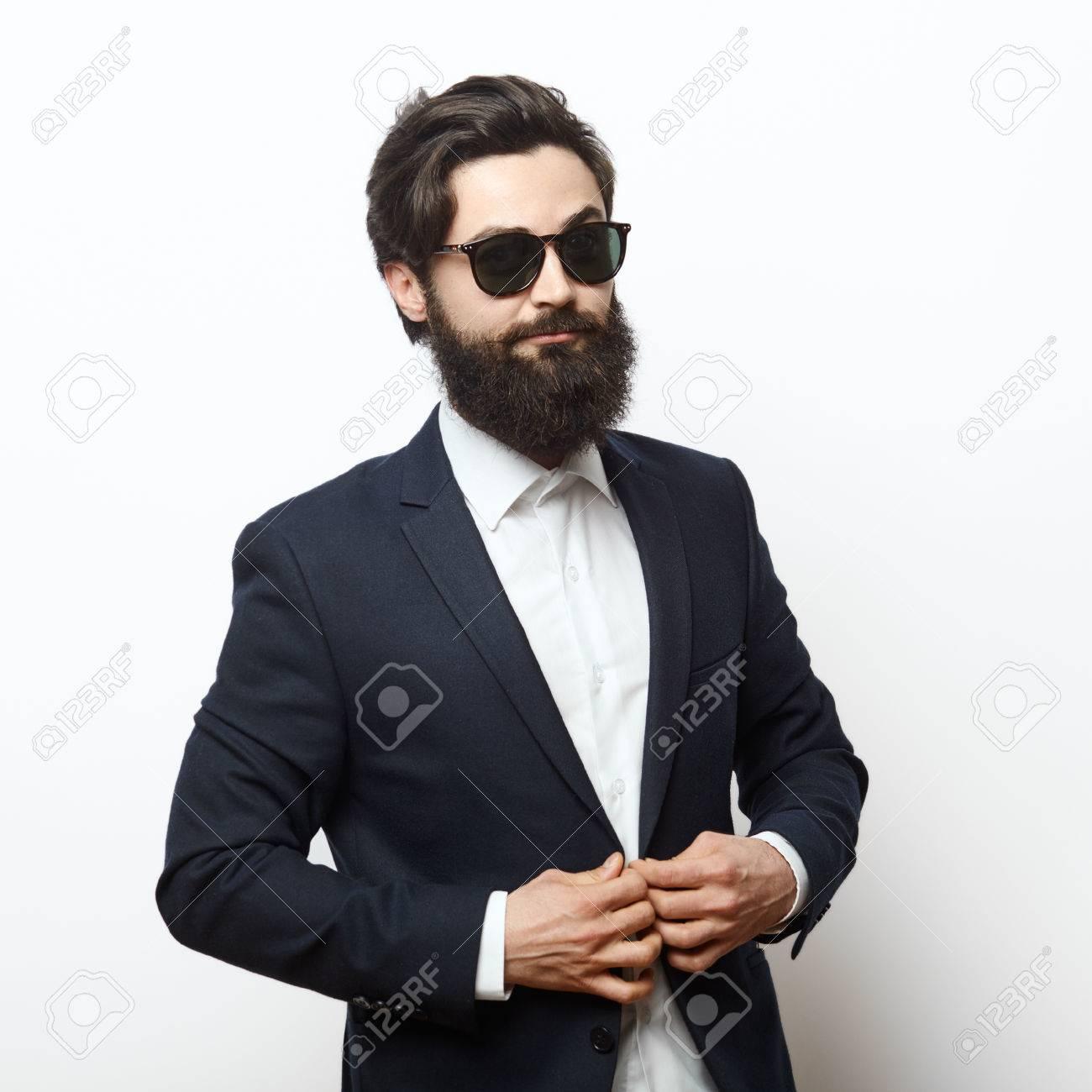 570657e02dd763 Standard-Bild - Stilvolle bärtigen gut aussehender Mann mit Sonnenbrille  und Befestigung intelligenten Anzug isoliert auf weißem Hintergrund