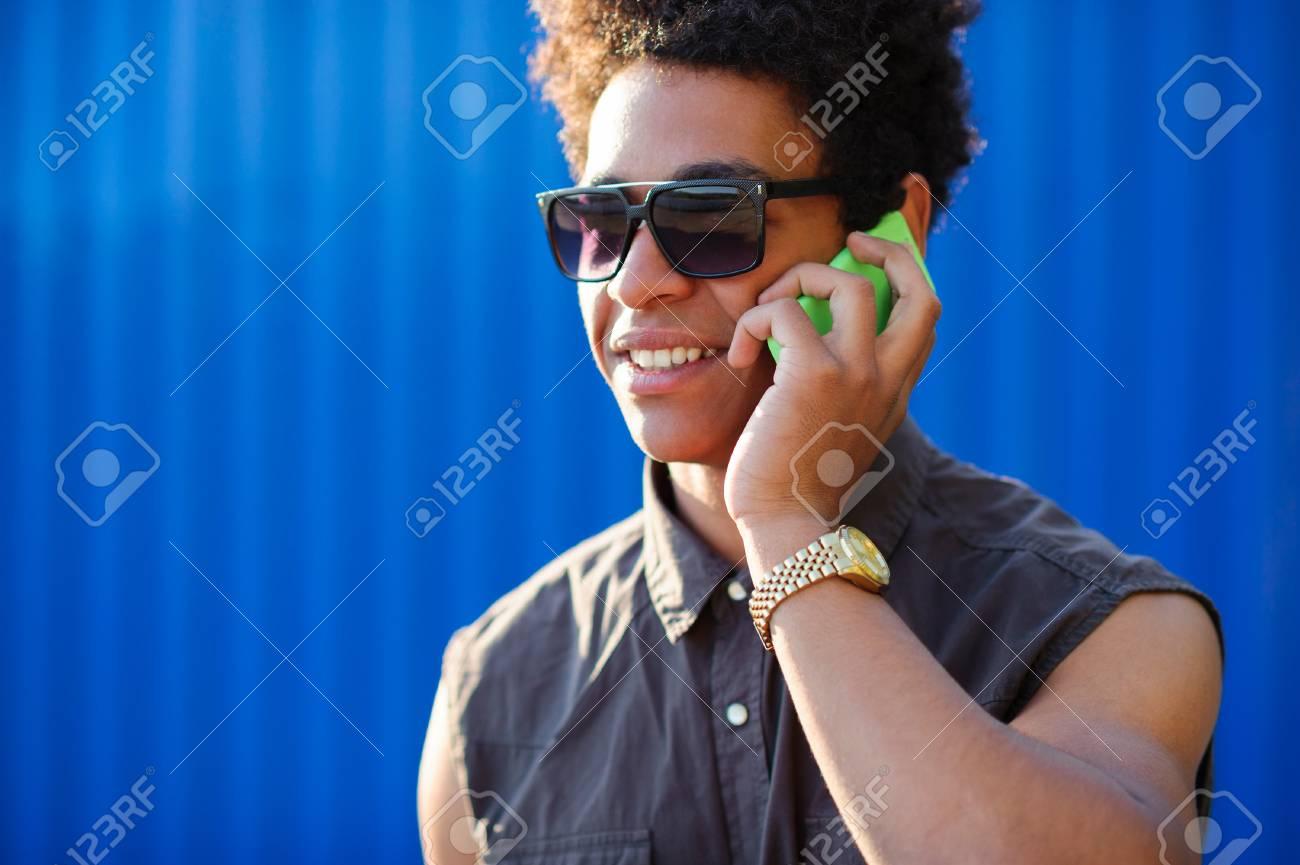 Sur EspaceGros Le Homme Fond Couleur Jeune Africain Copie Noir Téléphone Smartphone Parler De Bleu Heureux Plan D'un Avec Cellulaire ARj3Lq54