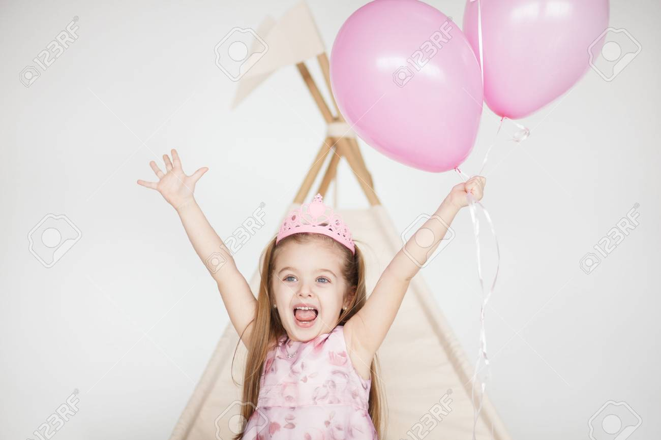 portrait of little baby girl smiling on the day of birth in a dress with colorful balloons. Excited kid celebrating her birthday - 60839123