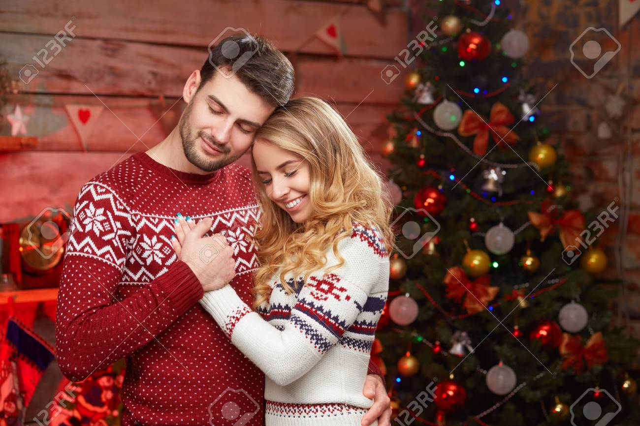A Wish For Christmas.Happy Couple In Love Over Christmas Tree Young Smiling Couple