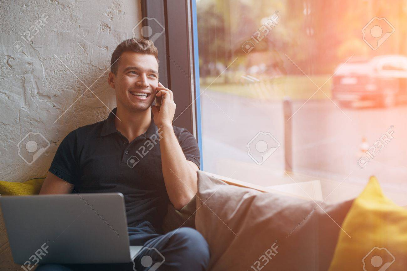 Happy young man using laptop and mobile phone on couch at home. Smiling handsome male talking on smartphone with sunlight flare effect. Toned colors - 65670358