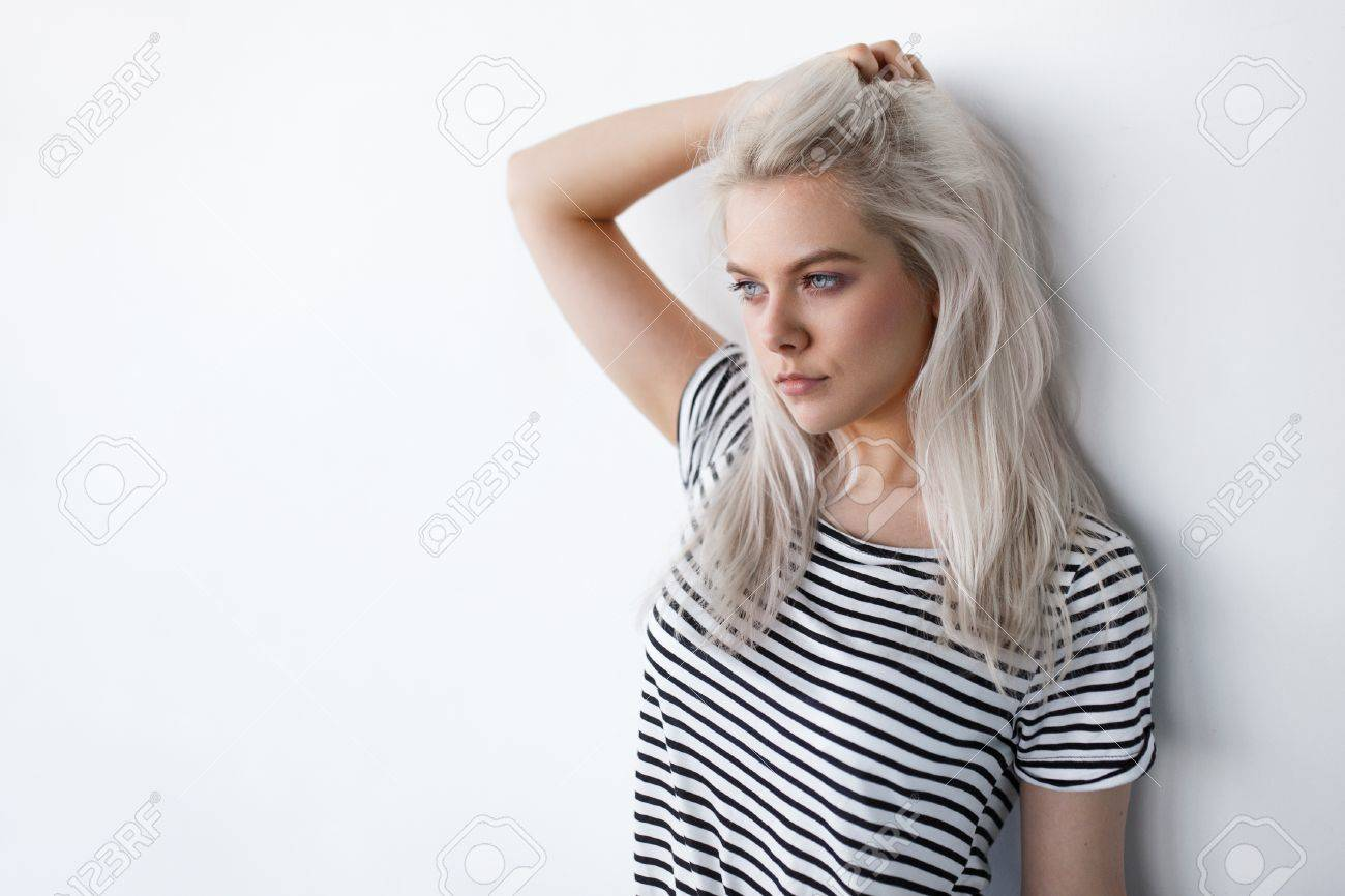 beautiful young blond woman posing while leaning on white wall with copy space. Hipster girl with blue eyes and bleached silver hair - 65686763