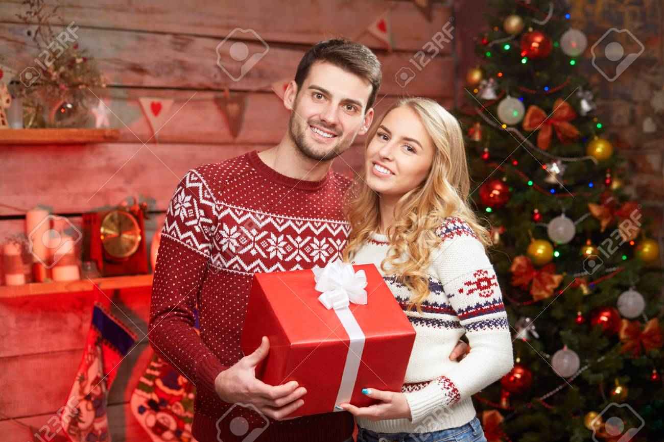 Happy Couple In Love Sharing Gifts At Christmas Tree Big Wrapped Red Box Stock Photo