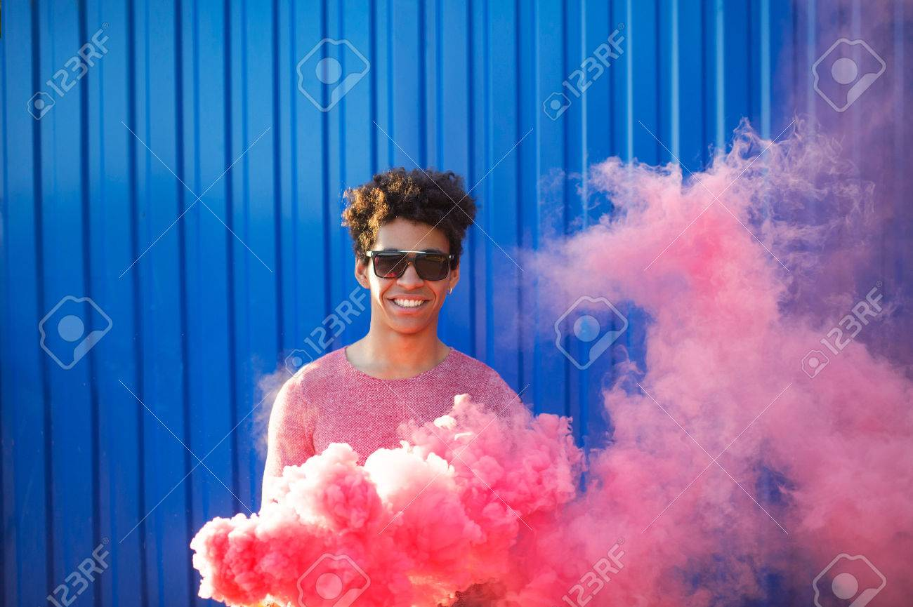 African American young man holding a smoke grenade. Colorful portrait of teenager hipster with red smoke on blue background. Stock Photo - 65691927