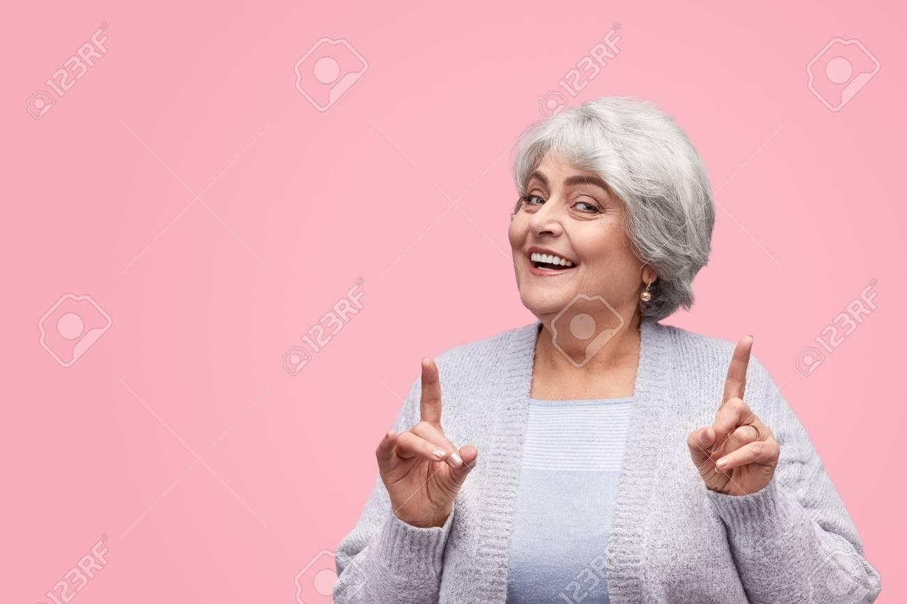 Cheerful senior female pointing up - 119338855