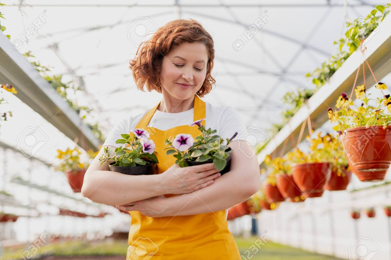 Female gardener embracing potted flowers - 125229080