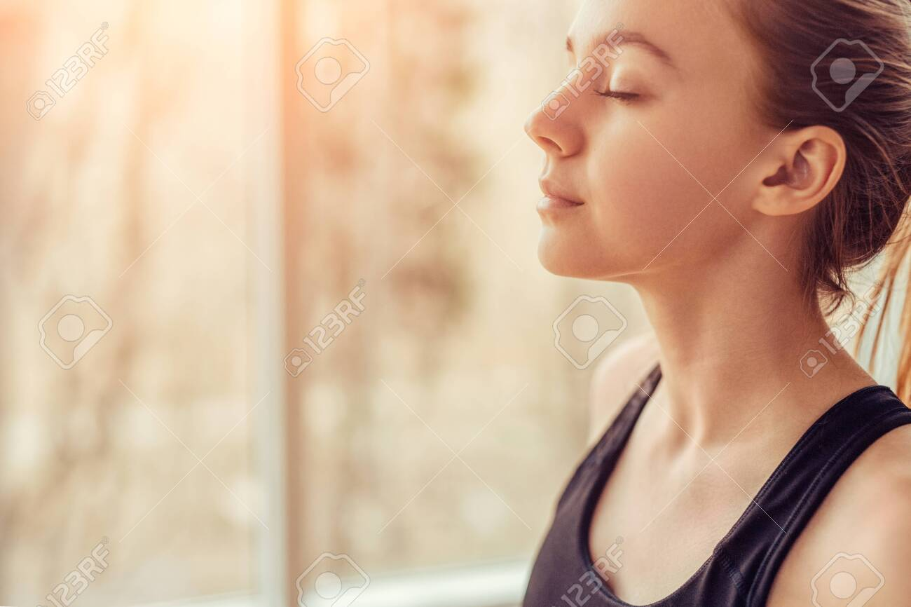 Young woman doing breathing exercise - 128958043