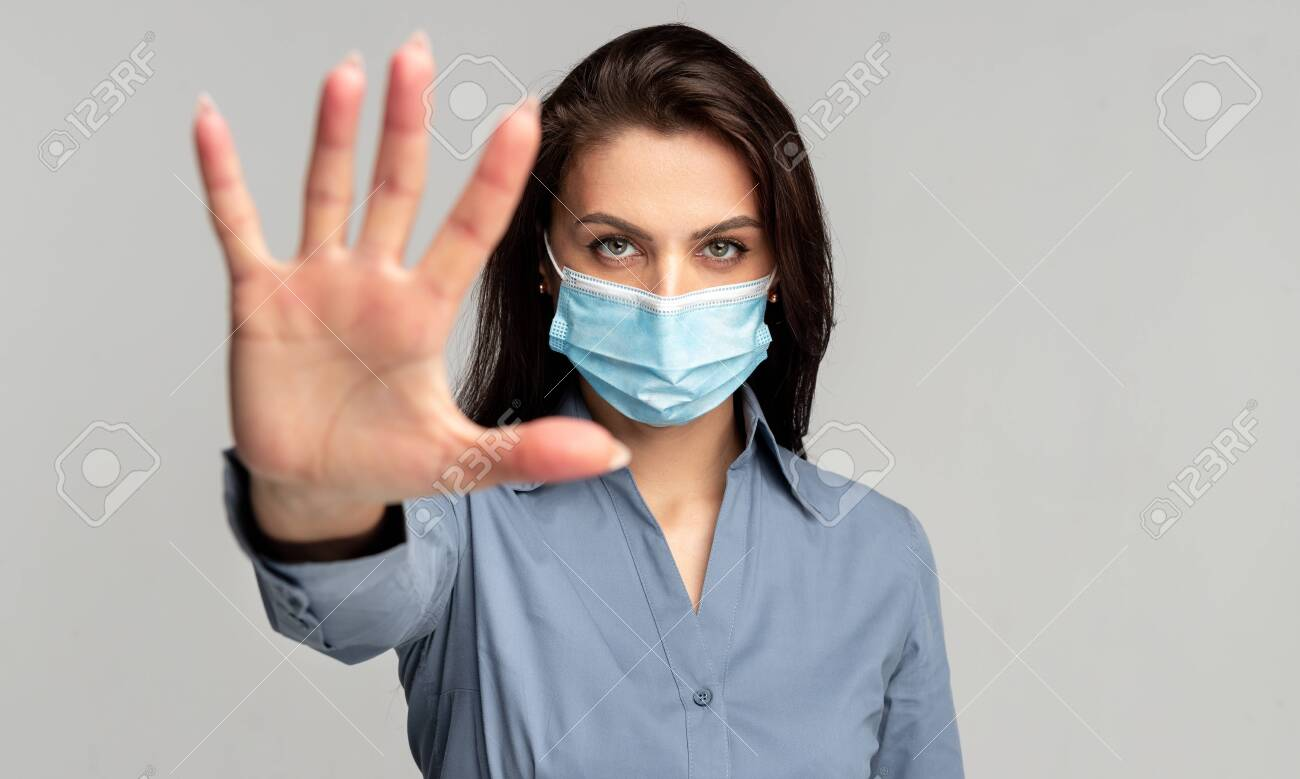 Young woman in protective mask making stop gesture - 148386820