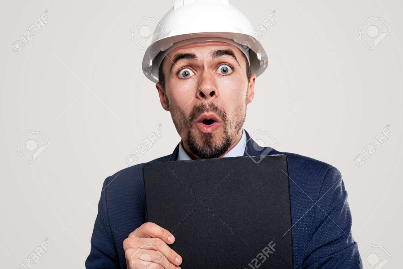 Shocked contractor with clipboard looking at camera - 164869221