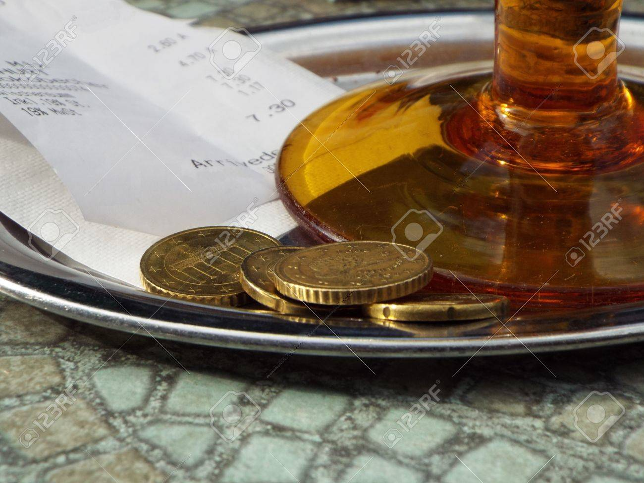 Tipping on a tray located under a brown glass a receipt alongwith loose change. - 40872356